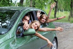 Cheerful young people having summer trip on a car.
